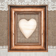 Stock Photo: Aged frame with wooden heart on burlap