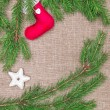 Christmas decoration with fir branches and red sock on burlap — Stock Photo