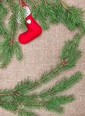 Vánoční dekorace s větvemi jedlí a červenou ponožku na pytlovina — Stock fotografie