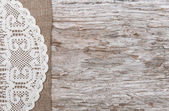 Old wood bordered by burlap and lacy cloth — Stock Photo