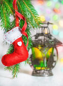 Christmas red sock on fir branch and lantern — Stock Photo