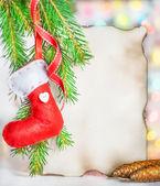 рождественская открытка с красный носок на ветке ели — Стоковое фото