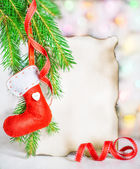 Christmas card with red sock on fir branch — Stock Photo