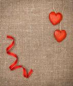 Wooden hearts on hessian — Stock Photo