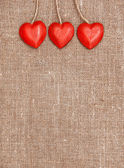 Wooden red hearts on hessian — Foto Stock