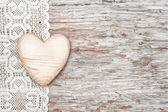 Wooden heart on lacy cloth and old wood — Stock Photo