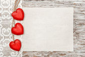 Wooden hearts, lacy cloth and canvas on old wood — Stock Photo