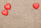 Wooden hearts on the burlap — Stock Photo