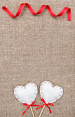 Textile hearts and ribbon on the burlap — Stock Photo
