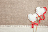 Textile hearts, ribbon and linen cloth on the burlap — Stock Photo