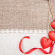 Wooden hearts, ribbon and linen cloth on the burlap — Stock Photo