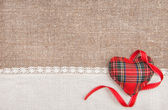 Textile heart, ribbon and linen cloth on the burlap — Stock Photo