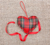 Textile heart and ribbon on sacking — Stock Photo