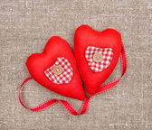 Textile hearts and ribbon on sacking — Stock Photo