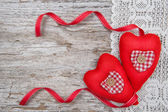 Valentine card with textile hearts on lace and old wood — Stock Photo