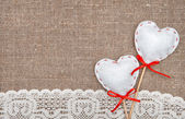 Textile hearts and lacy cloth on the burlap — Stock Photo