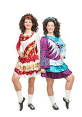 Two young women in Irish dance dresses posing isolated — Stock Photo