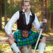 Handsome scottish man with sword and pipe — Stock Photo #41440827