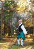 Handsome scottish man with sword  in the forest — Stock Photo