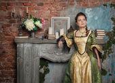 Beautiful woman in medieval dress near fireplace — Stock Photo