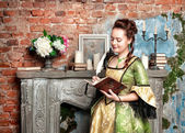 Beautiful woman in medieval dress writing in diary — Stock Photo