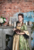 Beautiful woman in medieval dress with book and feather — Stock Photo