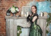 Beautiful woman in medieval dress near fireplace — Stockfoto