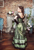 Beautiful woman in medieval dress near fireplace — Foto de Stock