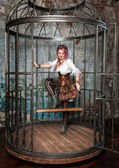 Beautiful steampunk woman in the cage — Stock Photo