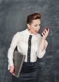 Angry business woman with laptop and mobile phone — Stock Photo