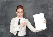 Woman pointing on drawing empty paper in her hand — Stockfoto
