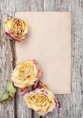 Dry roses and paper on the old wood — Stock Photo