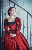 Beautiful woman in medieval dress on the stairway — Stock Photo