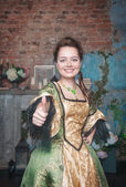 Woman in medieval dress showing thumbs up sign — Stockfoto