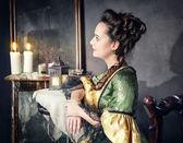 Beautiful woman in medieval dress near mirror — Foto Stock