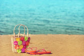 Slippers with wicker bag on the beach — Stock fotografie