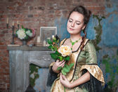 Beautiful woman in medieval dress with flower — Stock Photo
