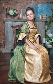 Beautiful woman in medieval dress on the chair — Stock fotografie