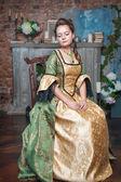 Piękna kobieta w średniowiecznych sukienka na krzesło — Zdjęcie stockowe