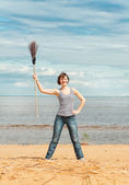 Funny woman with broom on the beach — Stock Photo