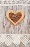 Wooden heart and lace fabric on the old wood — Стоковое фото
