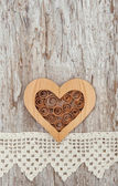 Wooden heart and lace fabric on the old wood — Stockfoto