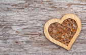 Wooden decorative heart on the old wood — Stockfoto