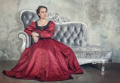 Beautiful woman in medieval dress on the sofa — Stockfoto