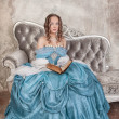 Beautiful woman in medieval dress with book on the sofa — Stock Photo #48716807