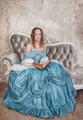Beautiful woman in medieval dress with book on the sofa — Foto Stock