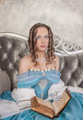 Beautiful woman in medieval dress with book on the sofa — Foto de Stock
