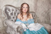 Beautiful woman in medieval dress on the sofa — Foto Stock