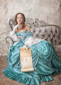 Krásná žena v středověkých šatech na pohovce — 图库照片