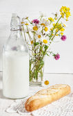 Fresh milk in old fashioned bottle with baguette — Stock Photo